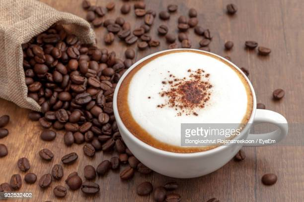 high angle view of cappuccino and beans on table - mocha stock photos and pictures