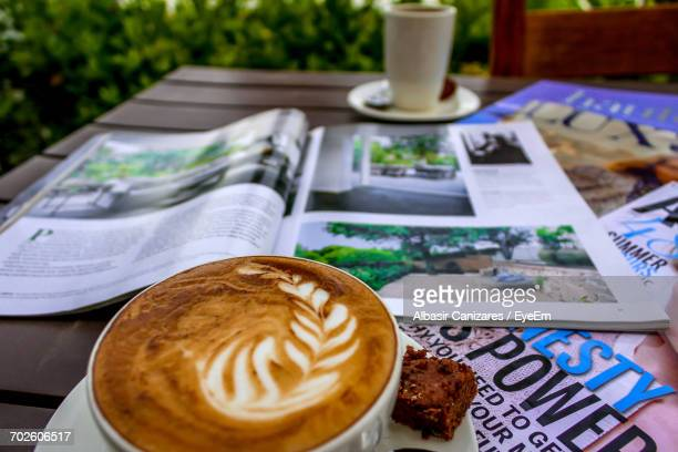 High Angle View Of Cappuccino And Magazines On Table In Yard