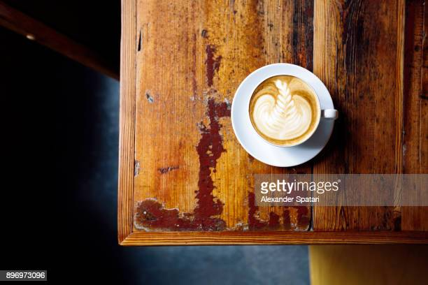 high angle view of cappuccino on wooden table - kaffee oder teepause stock-fotos und bilder