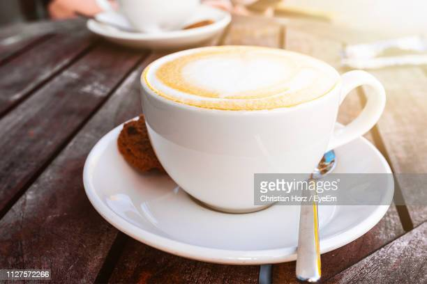 high angle view of cappuccino with cookie served on wooden table - kaffeetasse stock-fotos und bilder