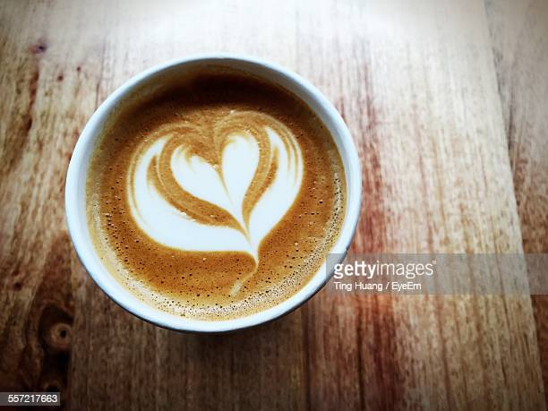 High Angle View Of Cappuccino With Heart Shape Pattern On Wooden Table