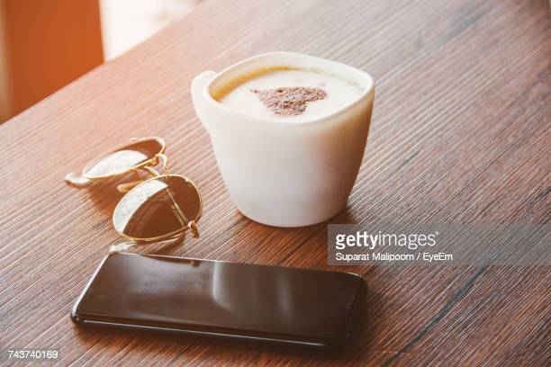 High Angle View Of Cappuccino With Mobile Phone And Sunglasses On Table At Home