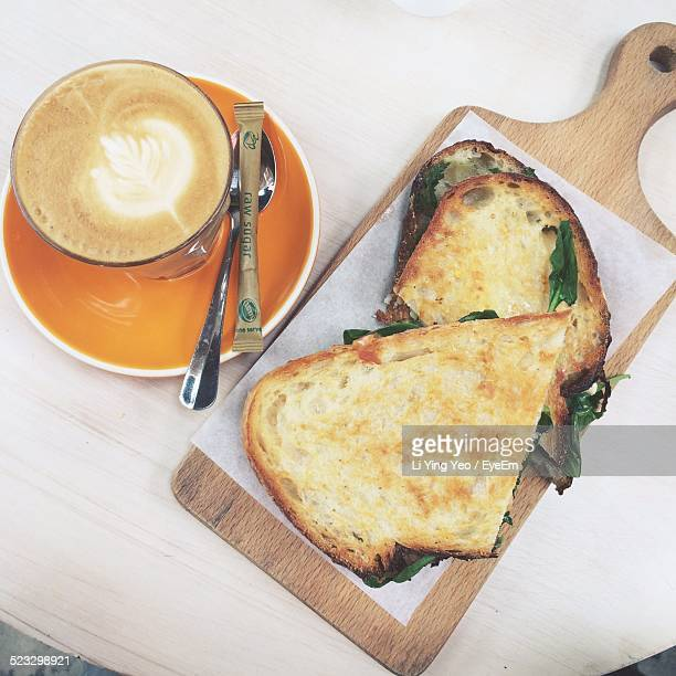 High Angle View Of Cappuccino With Sandwich Served On Table