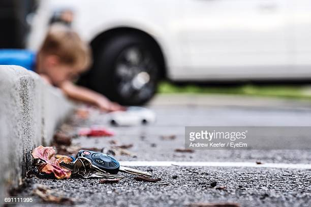 High Angle View Of Car Key On Street By Dry Leaf