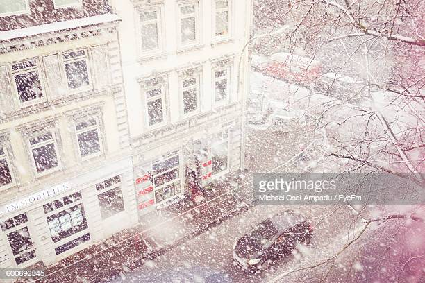 High Angle View Of Car On Street By Building During Snowfall