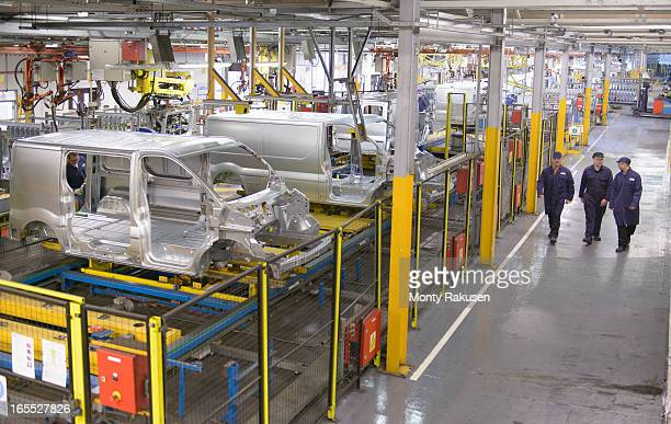 high angle view of car workers walking in car plant - luton stock pictures, royalty-free photos & images