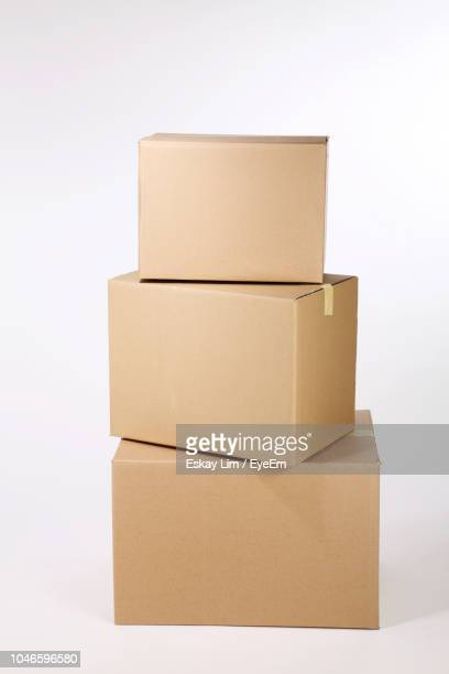 high angle view of cardboard boxes against white background - three objects stock pictures, royalty-free photos & images