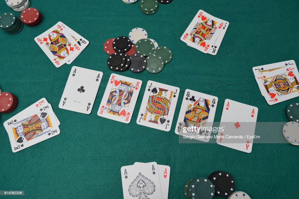 High Angle View Of Cards With Gambling Chips On Table : Stock Photo