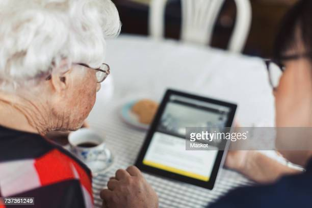 High angle view of caretaker and senior woman using digital tablet at home