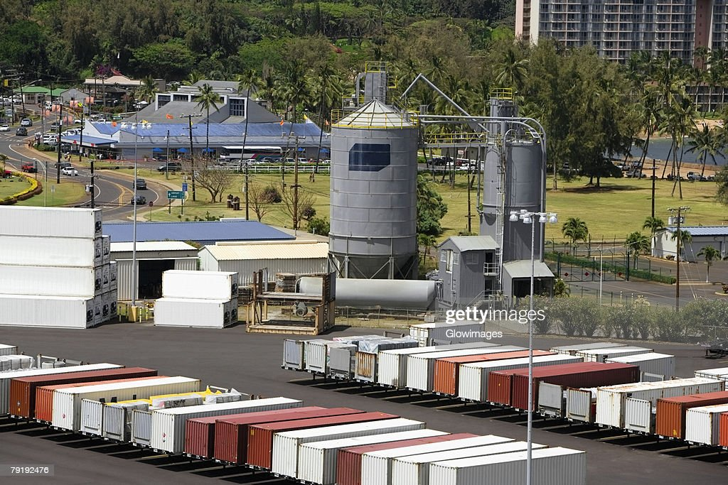 High angle view of cargo containers and a storage tank at a commercial dock : Foto de stock