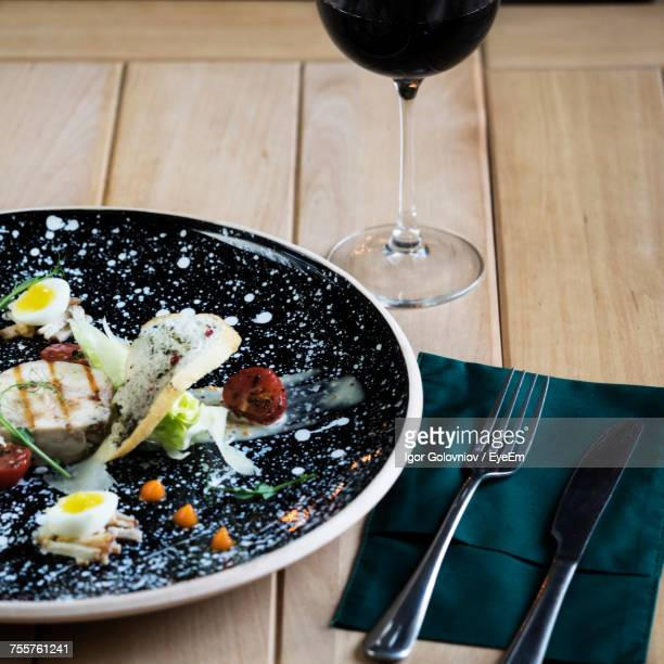 High Angle View Of Carpaccio With Salad Served In Plate By Wineglass On Table