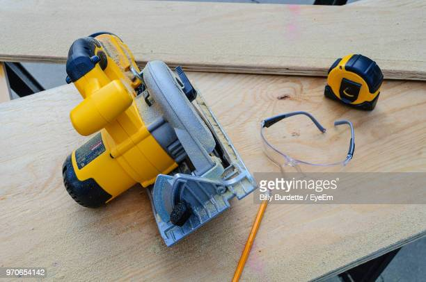 high angle view of carpenter tools on plank at workshop - circular saw stock photos and pictures