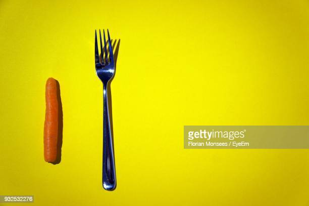 High Angle View Of Carrot And Fork Over Yellow Background
