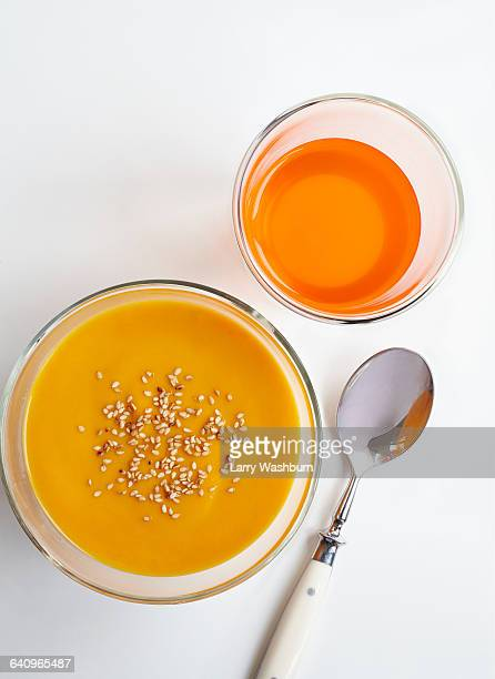 high angle view of carrot puree and drink with spoon over white background - pureed stock photos and pictures