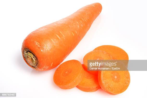 high angle view of carrot with slices against white background - carrot stock pictures, royalty-free photos & images