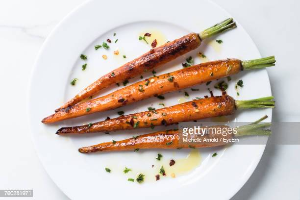 high angle view of carrots in plate - roasted stock pictures, royalty-free photos & images