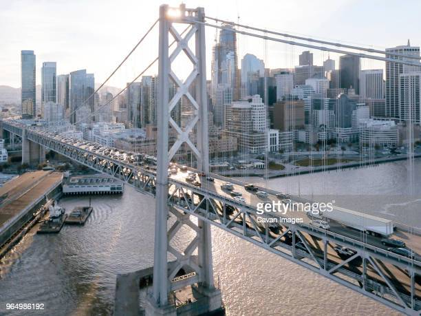 high angle view of cars moving on oakland bay bridge over sea against sky in city - oakland california stock pictures, royalty-free photos & images