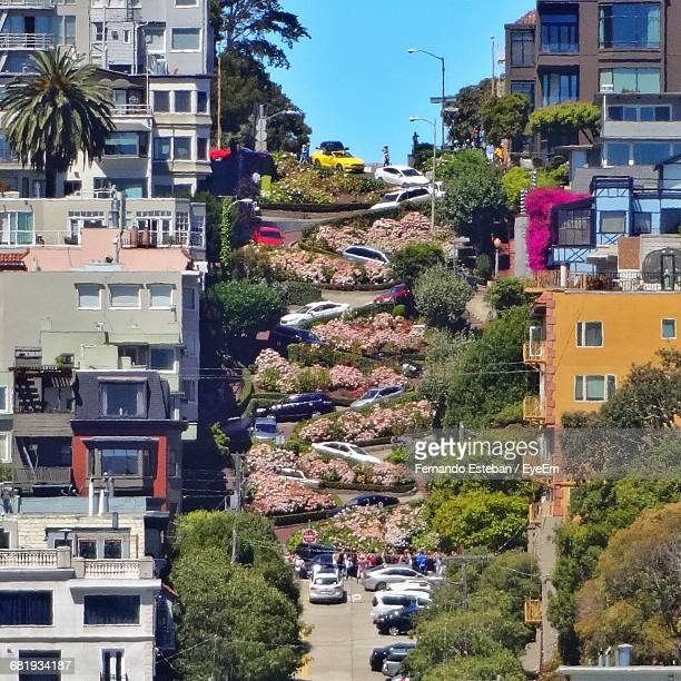 high angle view of cars on lombard street amidst buildings - lombard street san francisco stock pictures, royalty-free photos & images