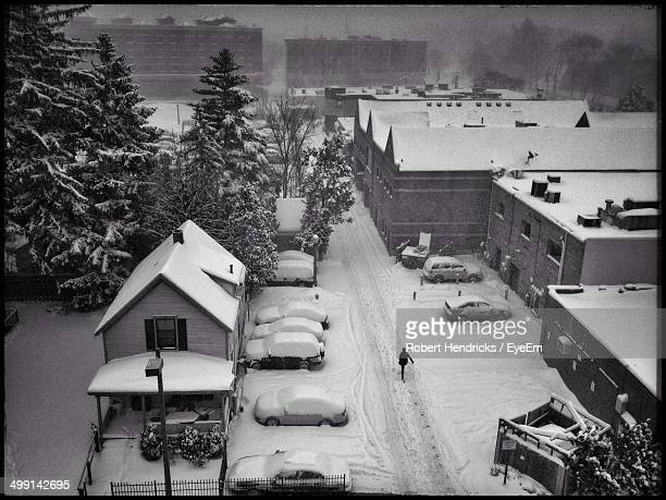 High angle view of cars on snow covered road by houses