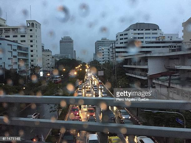 High Angle View Of Cars On Street In City Seen Through Wet Window In Rainy Season