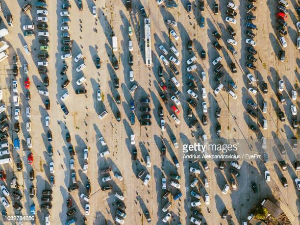 high angle view of cars parked on road in city - parkplatz stock-fotos und bilder