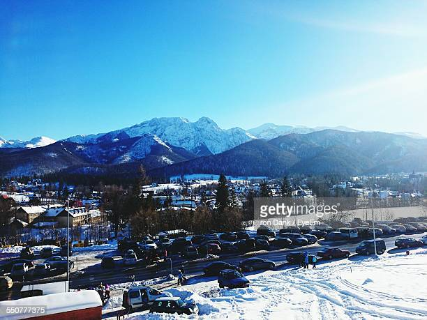 High Angle View Of Cars Parked On Snow Field In Front Of Mountains Against Blue Sky