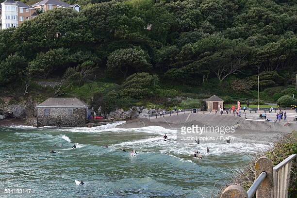 high angle view of caswell bay against trees - gower peninsula stock photos and pictures