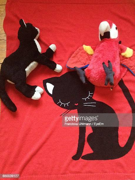 High Angle View Of Cat And Parrot Stuffed Toys On Bed