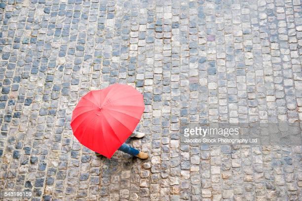 High angle view of Caucasian couple walking under heart shape umbrella
