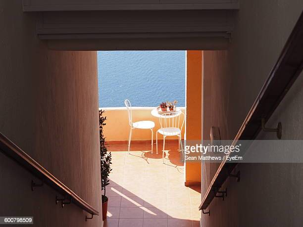 High Angle View Of Chair And Table At Balcony Seen From Doorway