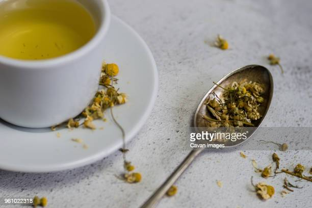 high angle view of chamomile tea in cup by spoon on table - chamomile tea stock photos and pictures