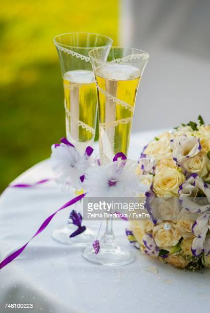 High Angle View Of Champagne Flutes By Bouquet On Table During Wedding