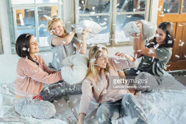High Angle View Of Cheerful Friends Playing Pillow Fight On Bed At Home