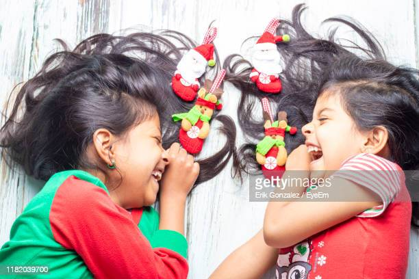 high angle view of cheerful sisters laughing while lying on hardwood floor - children only stock pictures, royalty-free photos & images