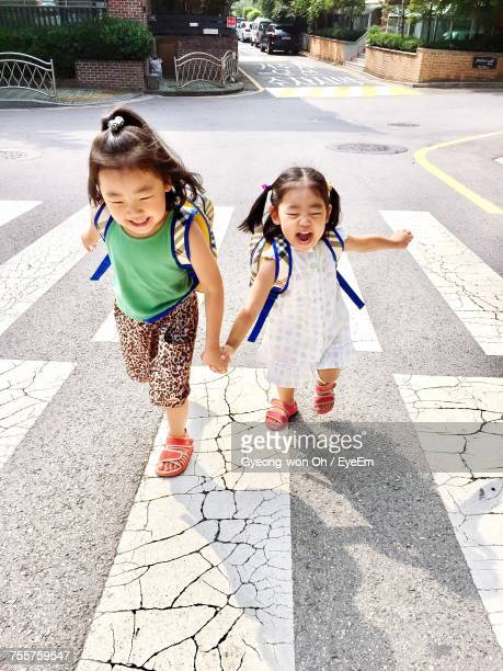 High Angle View Of Cheerful Sisters With Backpacks Running On Zebra Crossing