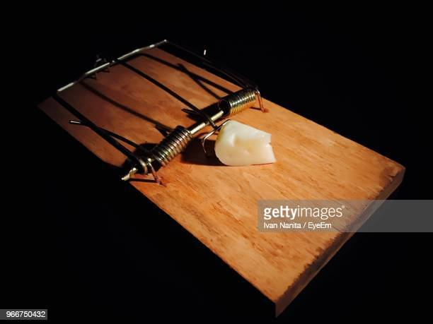 High Angle View Of Cheese On Mousetrap Over Black Background