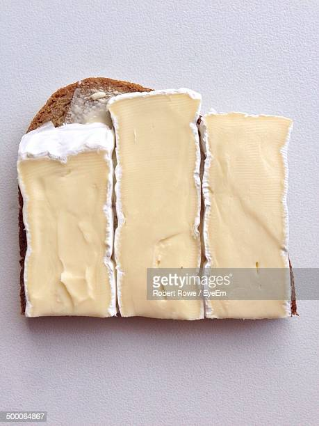 high angle view of cheese pieces on bread - camembert stock photos and pictures