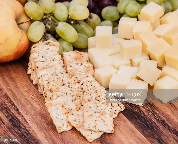 high angle view of cheese with crackers and fruits on table - cracker snack stock photos and pictures