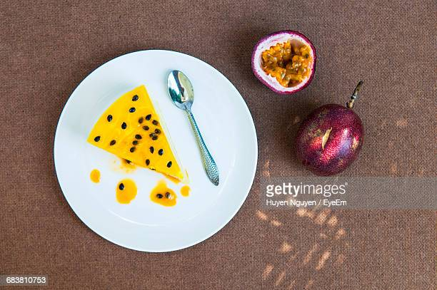 High Angle View Of Cheesecake In Plate By Passion Fruits