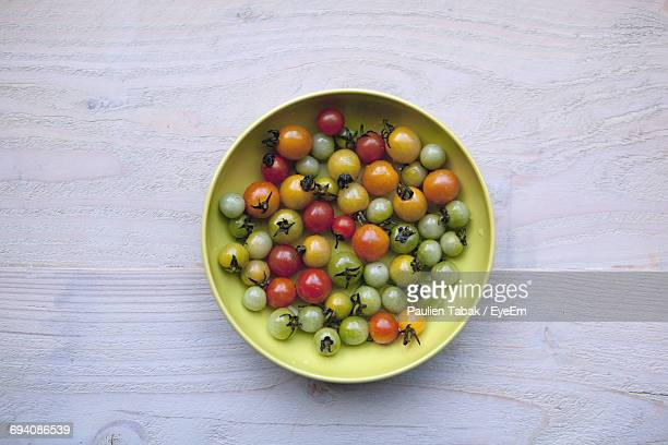 high angle view of cherry tomatoes in plate - paulien tabak stock-fotos und bilder