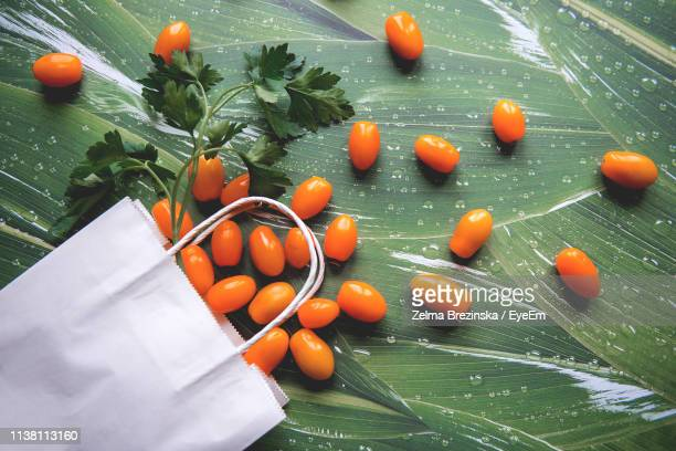 High Angle View Of Cherry Tomatoes With Herbs And Shopping Bag On Table
