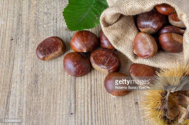 high angle view of chestnuts on table - chestnut food stock pictures, royalty-free photos & images