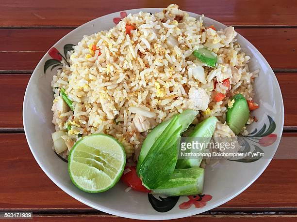 High Angle View Of Chicken Fried Rice Served With Cucumber And Lemon Slice