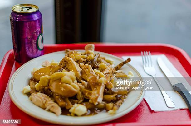 High Angle View Of Chicken Poutine Served In Plate With Drinking Can On Tray