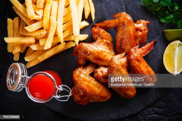High Angle View Of Chicken Wings With French Fries On Slate