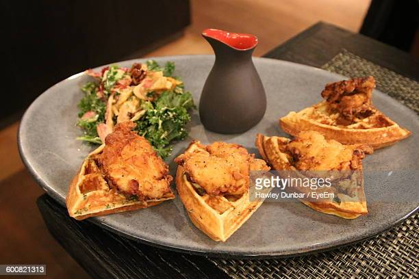 high angle view of chicken with waffles served in plate on table - chicken and waffles stock photos and pictures