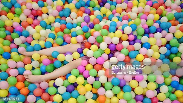 High Angle View Of Child Lying Down In Ball Pit