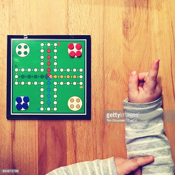 High Angle View Of Child Playing Ludo On Wooden Table