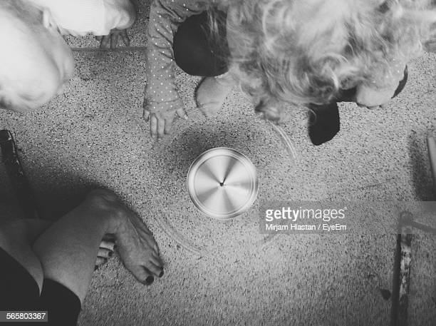High Angle View Of Child Playing With Spinning Top On Floor