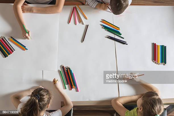 high angle view of children drawing on papers at table - color pencil stock pictures, royalty-free photos & images
